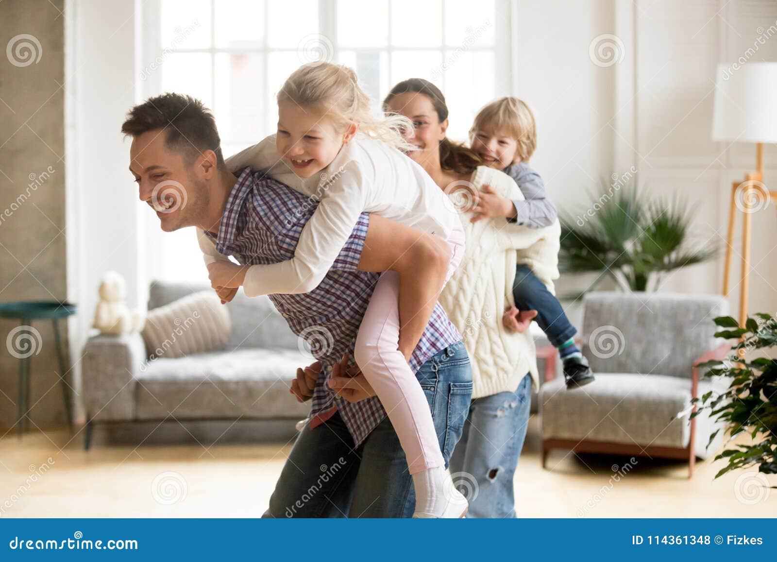 Papá cariñoso que lleva a cuestas a la pequeña hija que juega con la familia en h