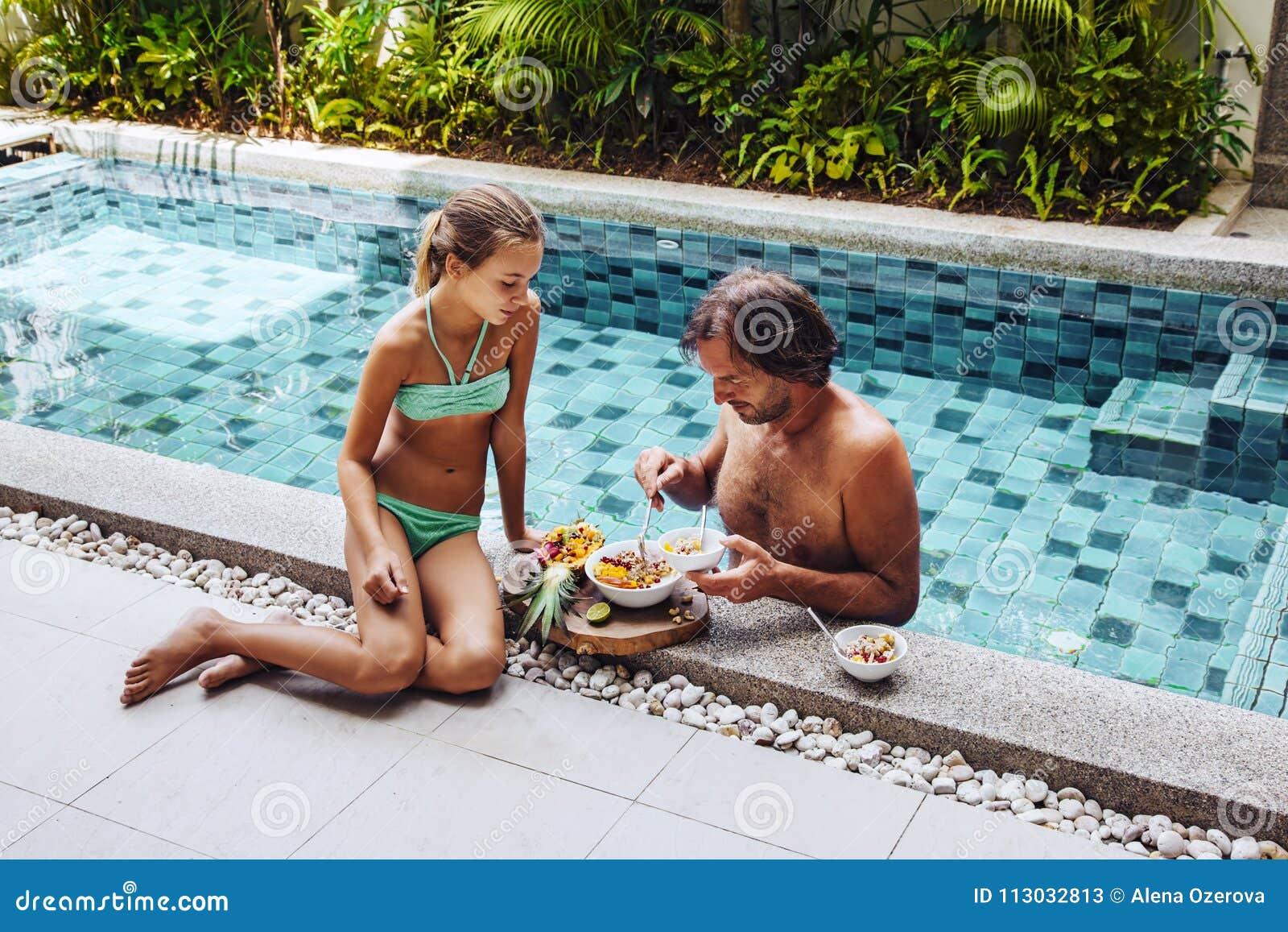 Papá con el niño que desayuna en la piscina