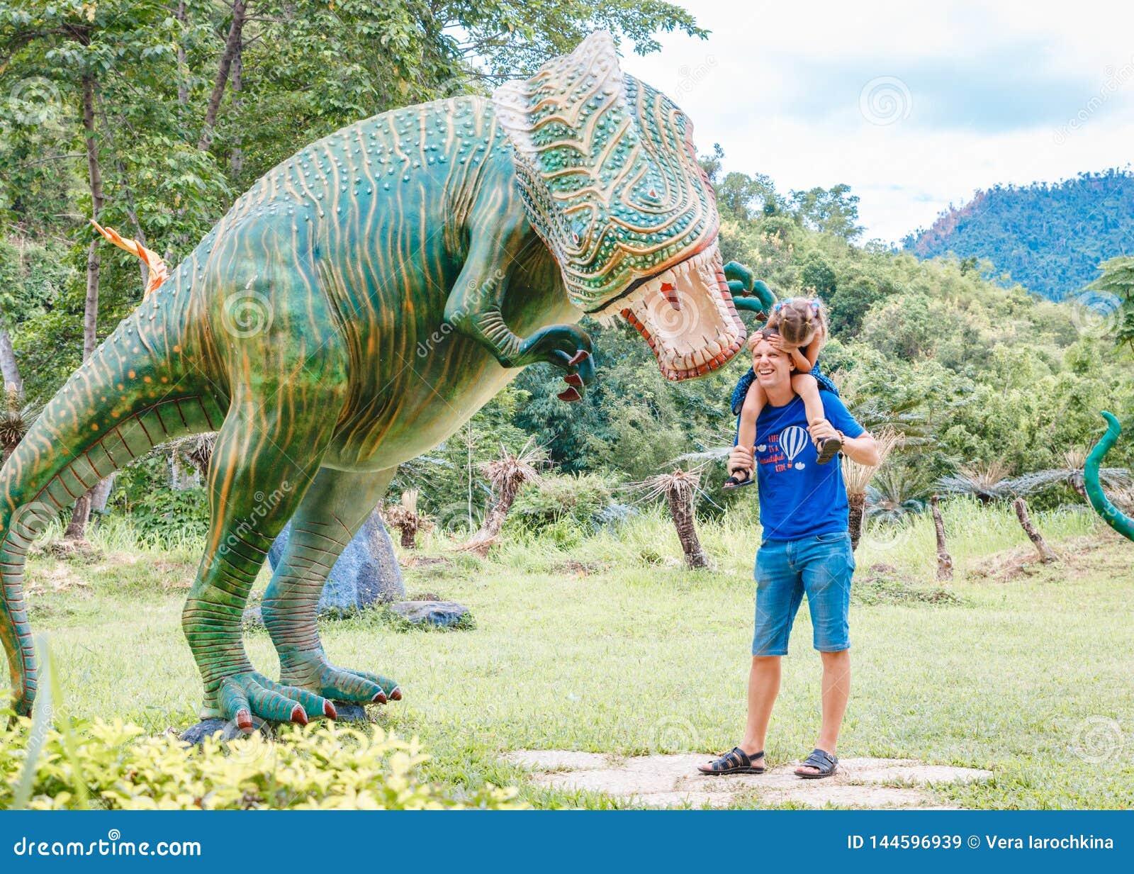 Papá con la pequeña hija cerca del dinosaurio verde grande en el parque en un día soleado Yang Bay, Vietnam