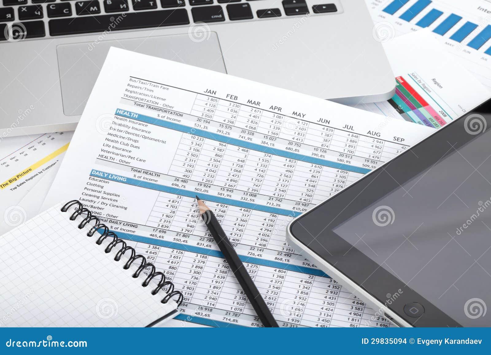 Papéis, computador e materiais de escritório financeiros