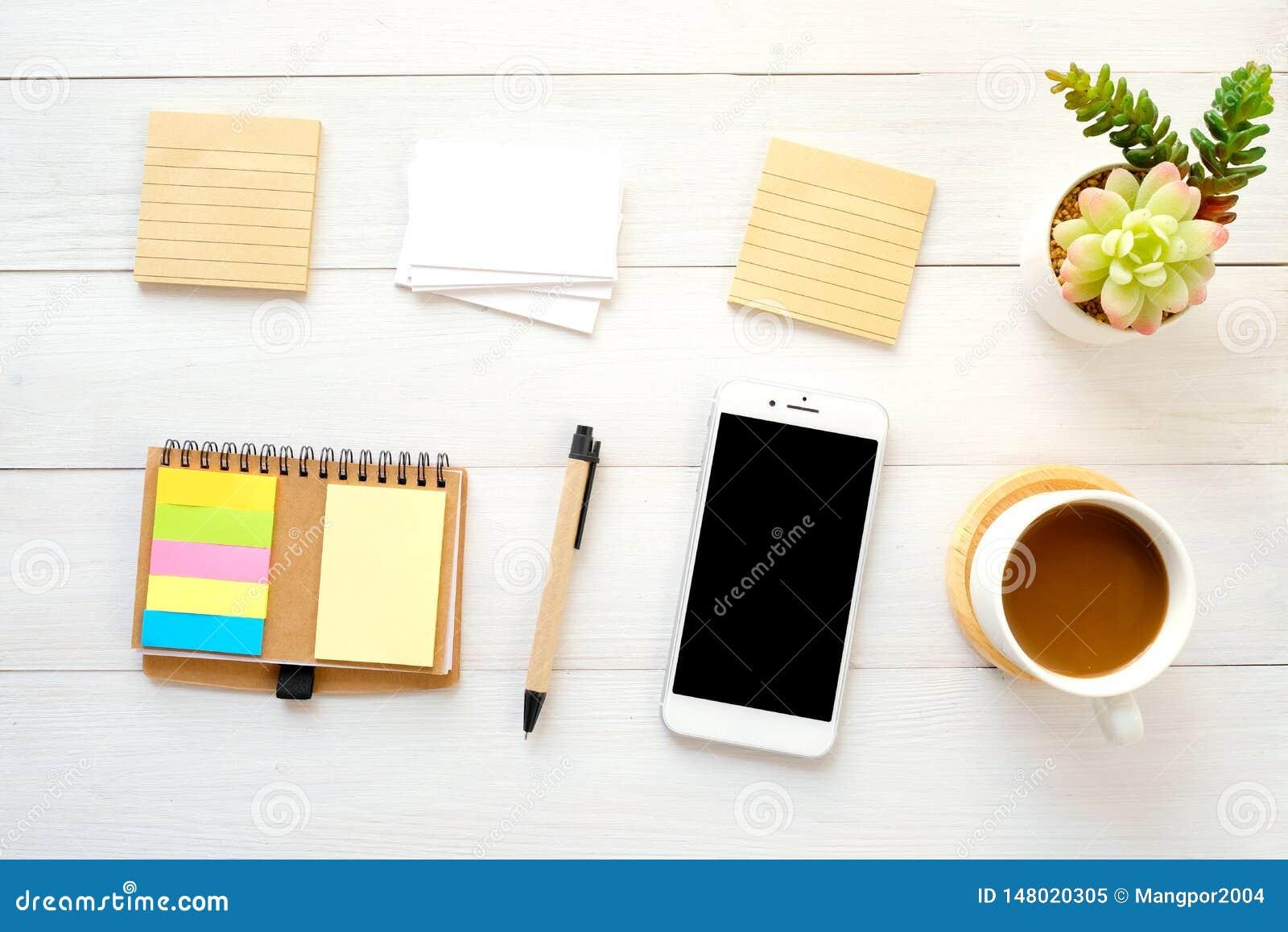 Papéis de nota vazios, cartão, telefone esperto, pena e café no fundo de madeira branco da tabela, com espaço da cópia para o tex