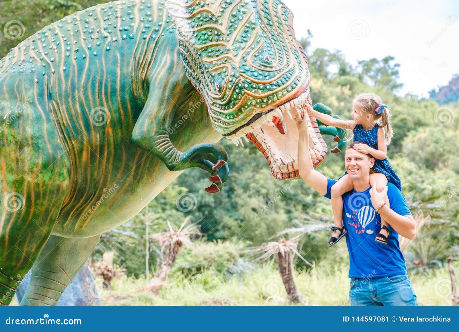 Pap? con la peque?a hija cerca del dinosaurio verde grande en el parque en un d?a soleado Yang Bay, Vietnam