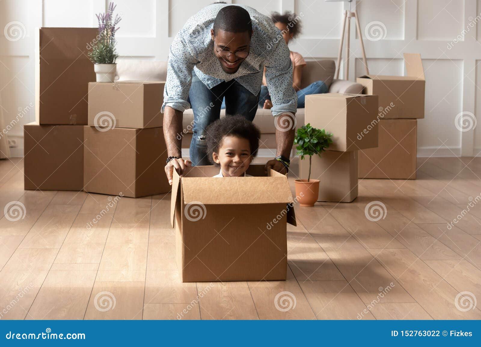 Papa africain heureux jouant avec peu d équitation de fils dans la boîte