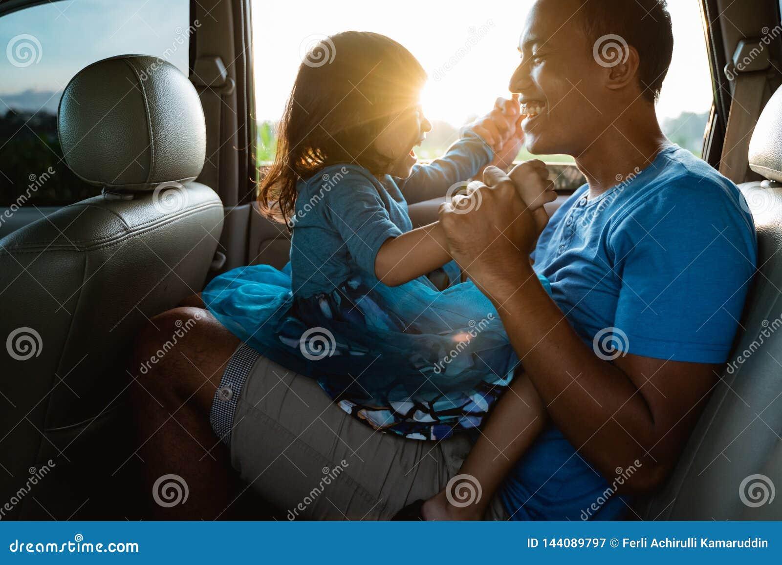 Papa chatouillant sa petite fille dans la voiture