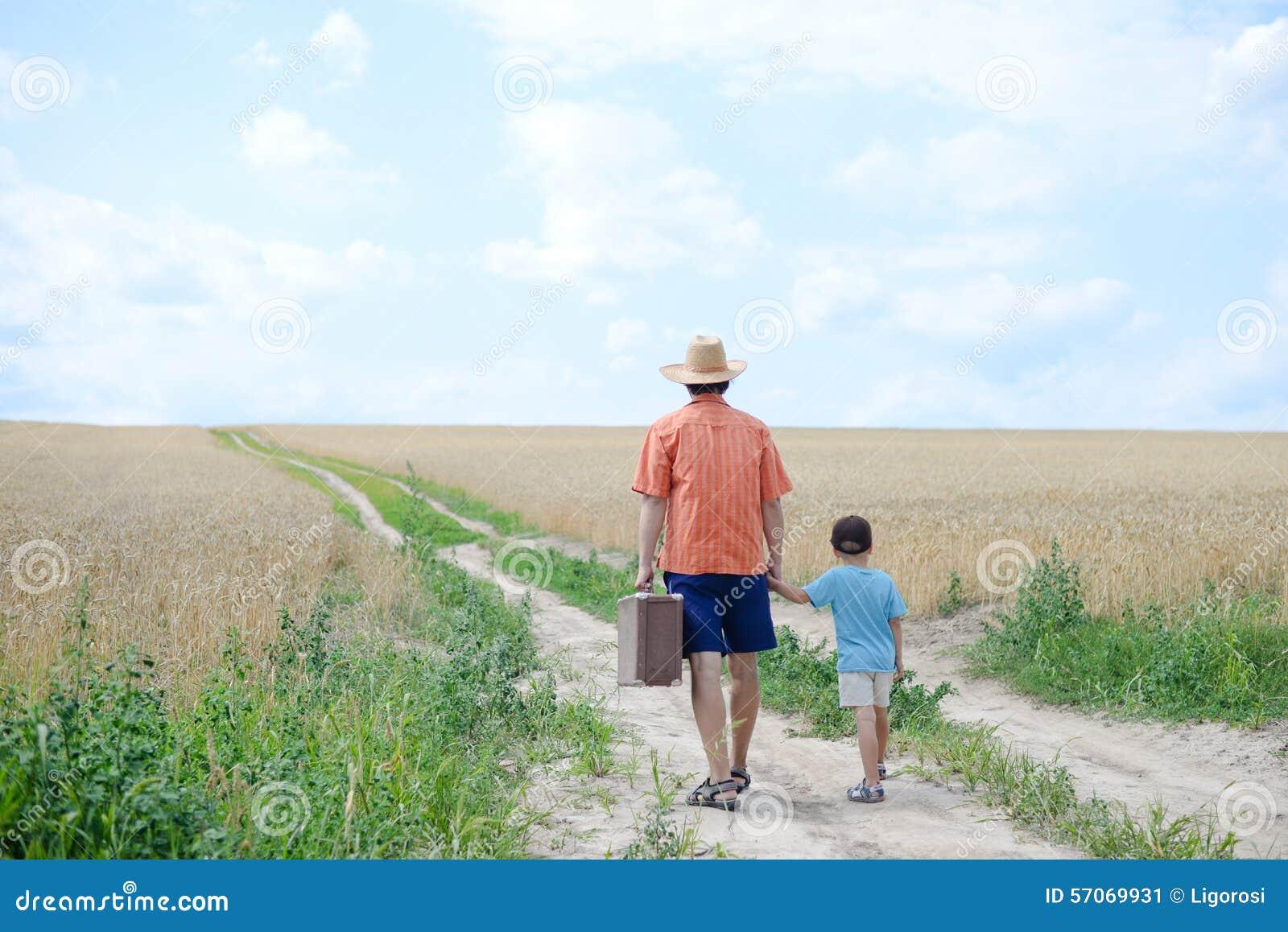 Papa die met koffer zijn zoon houden met de hand lopend