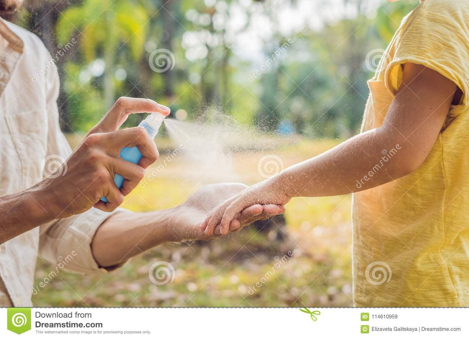 Papa en zoons de nevel van de gebruiksmug Bespuitend insektenwerend middel op huid openlucht