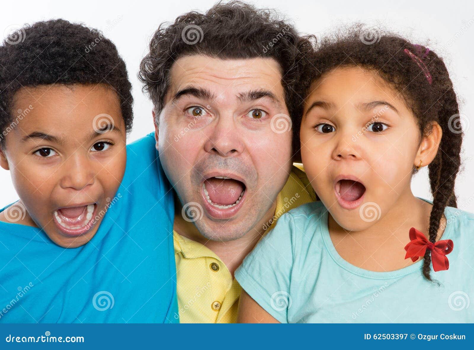 Papa et enfants étonnés avec la bouche grande ouverte