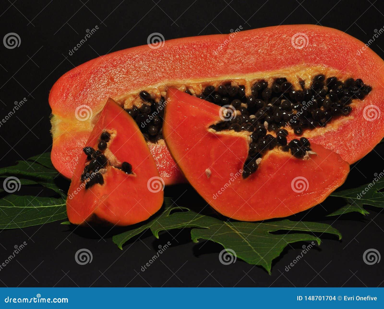 Papajafruit dat op zwarte achtergrond wordt ge?soleerd