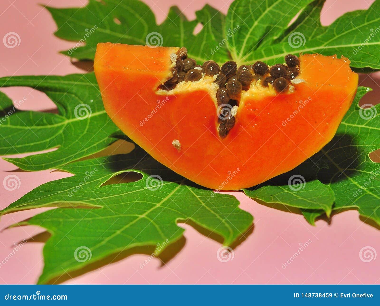 Papajafruit op roze achtergrond wordt ge?soleerd die