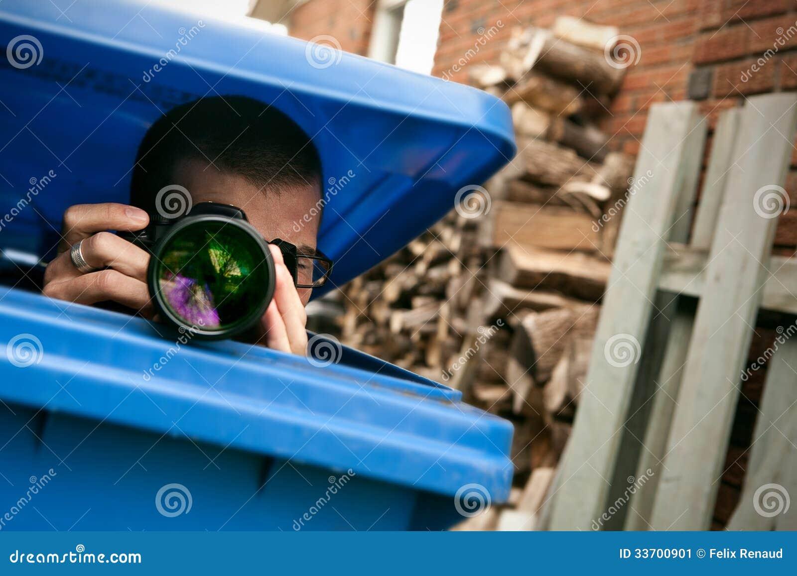 Paparazzi que escondem em um escaninho de lixo azul