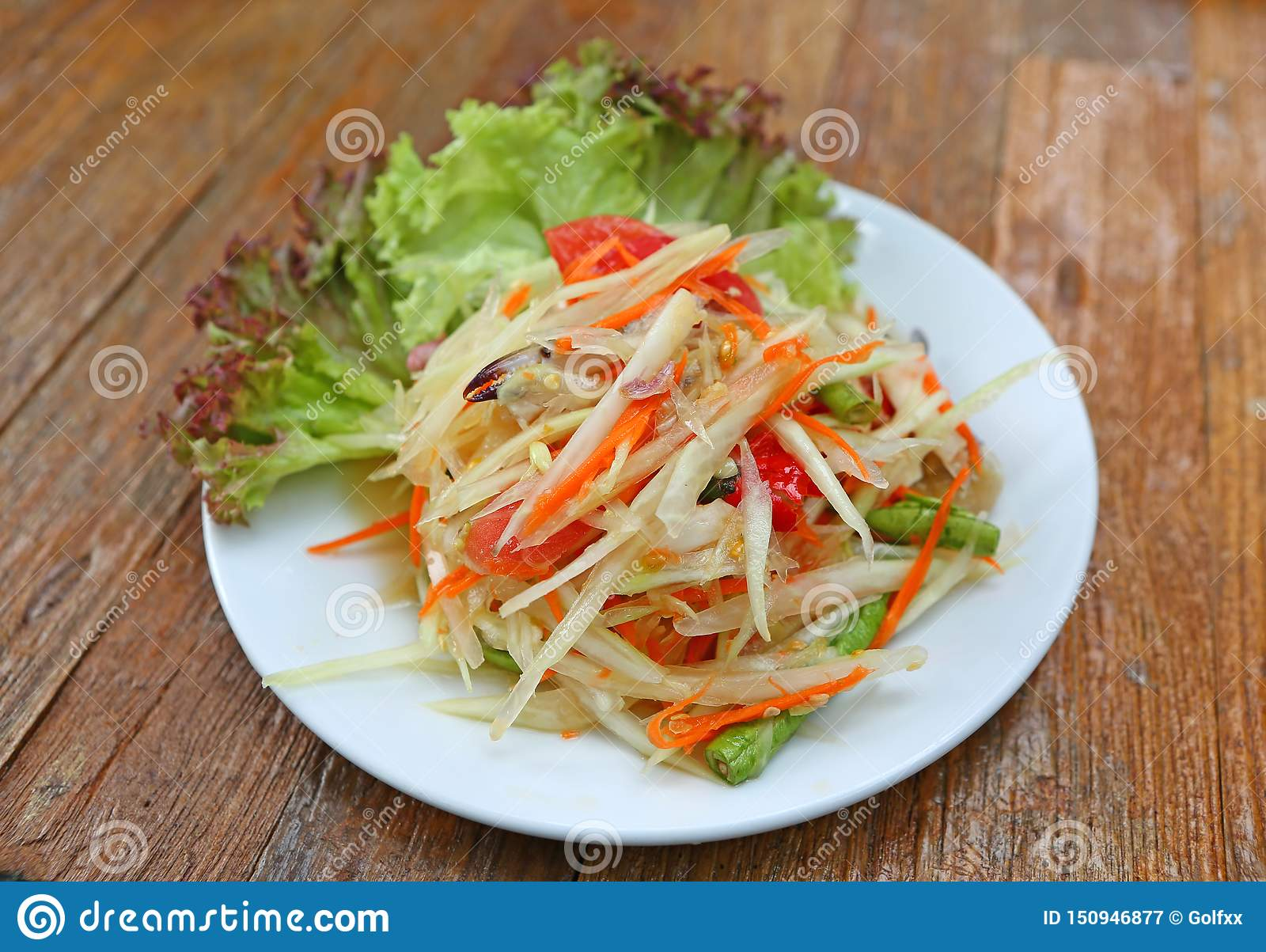Papaya salad with crab in white plate on wood table