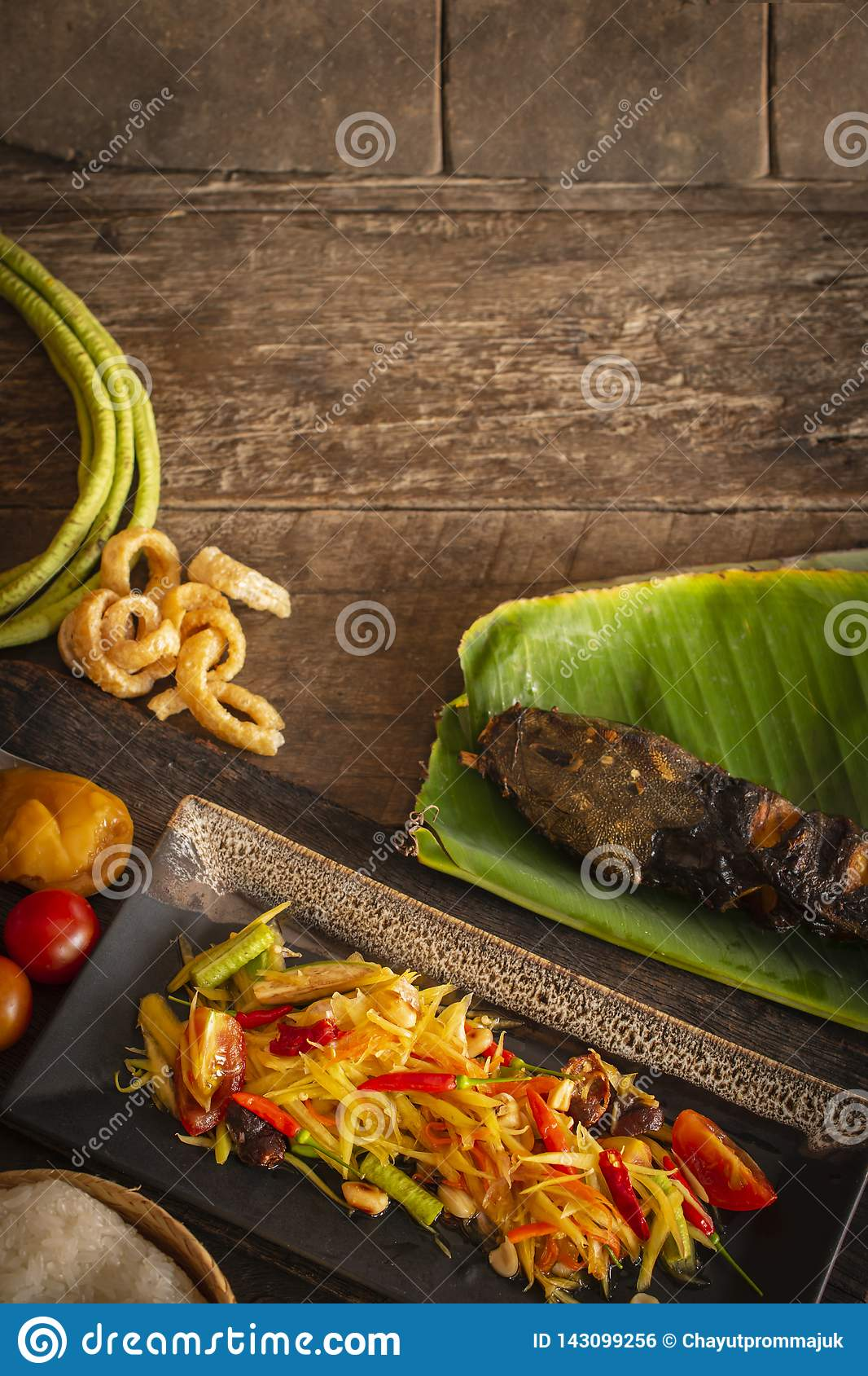 Papaya Salad Som tum Thai on square black plate placed on the wood table there are long bean, palm sugar, grilled fish, sticky