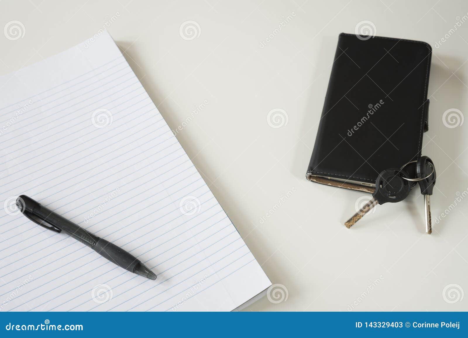 Papel alinhado com pena preta, chaves e smartphone, na mesa branca Espaço para o texto