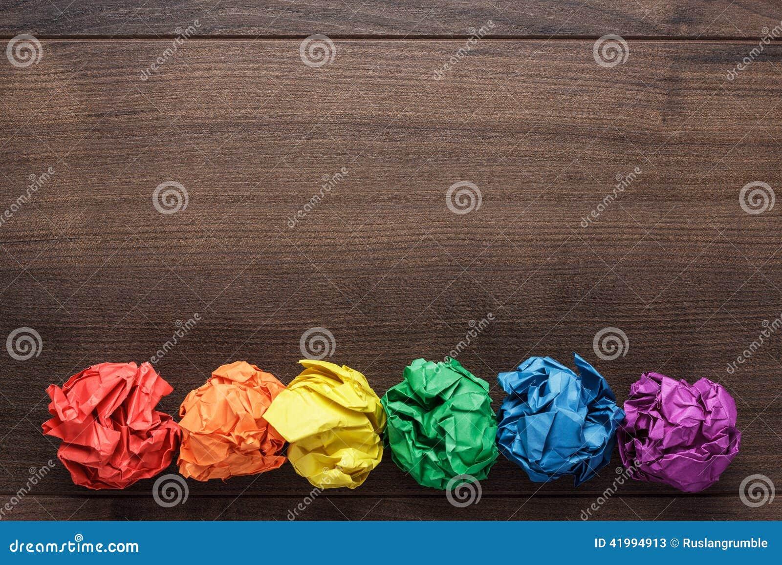Papel colorido amarrotado no fundo de madeira