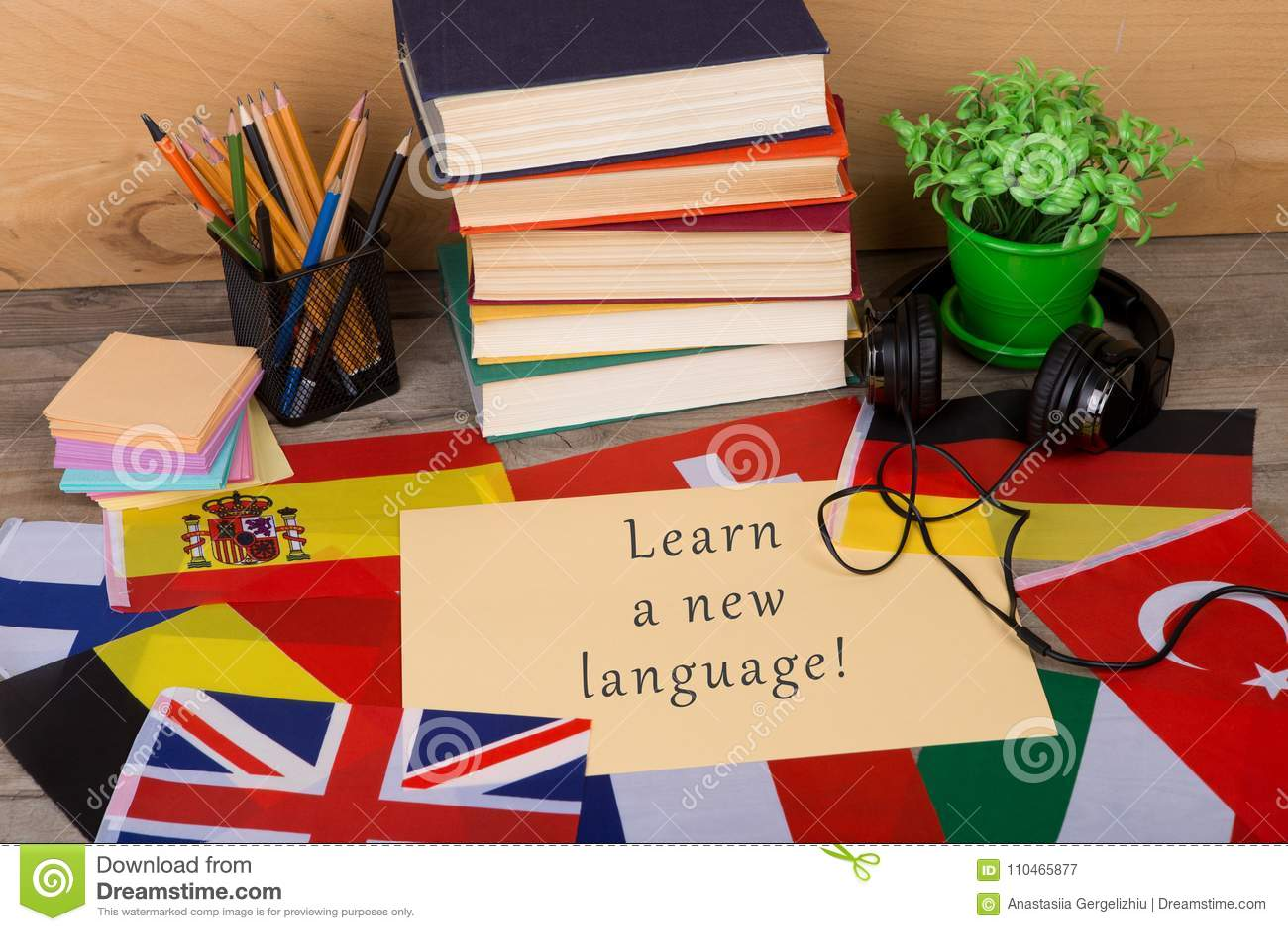 Papel com texto & x22; Aprenda uma língua nova! & x22; , bandeiras, livros, fones de ouvido, lápis