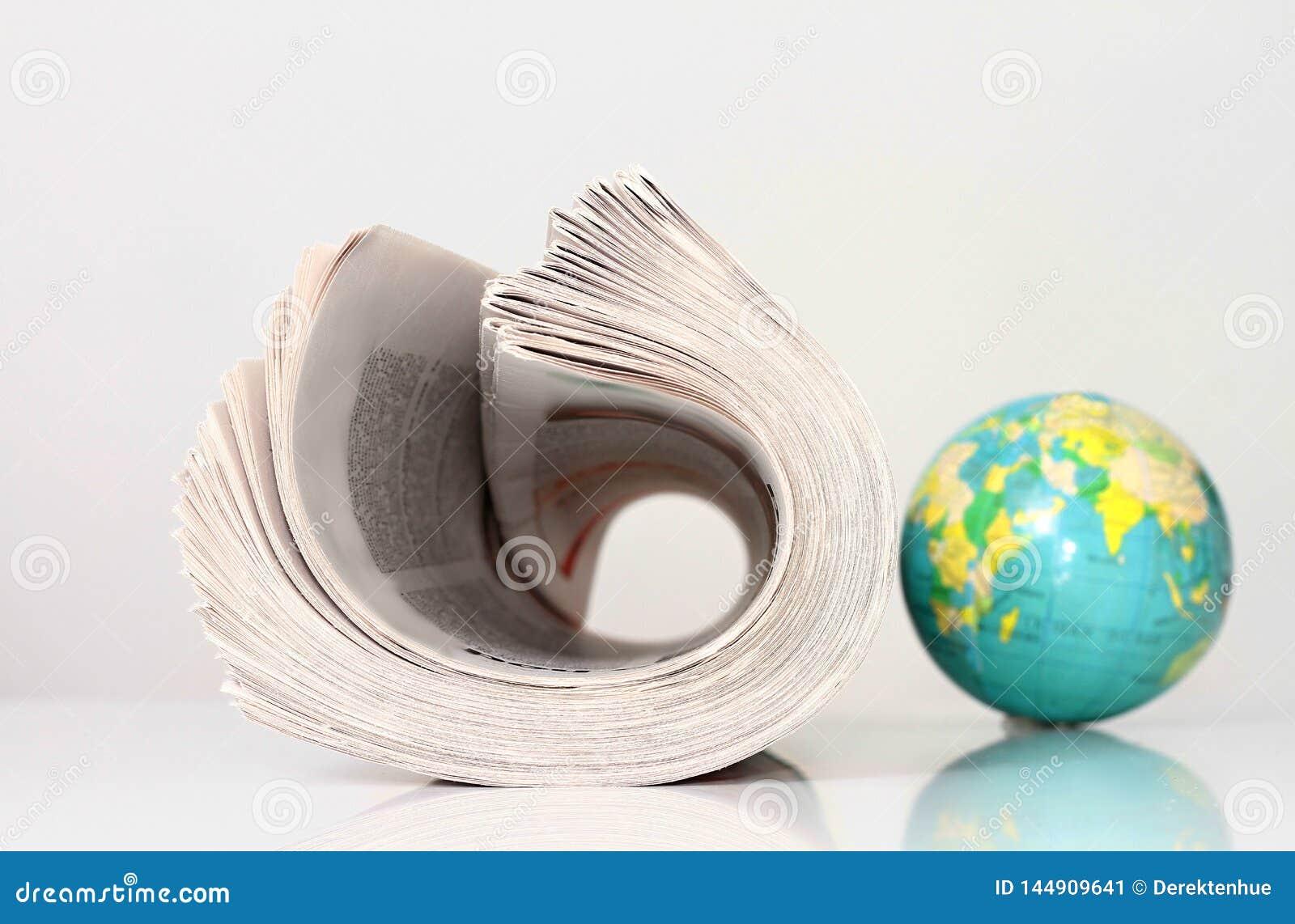 Papel da notícia com globo em uma tabela