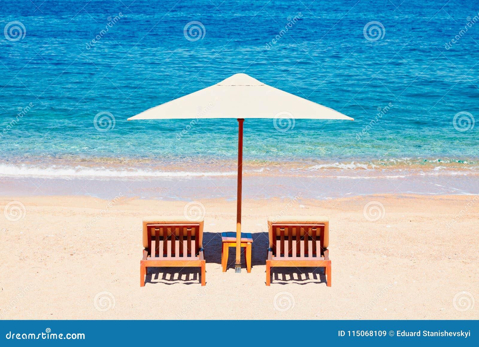 Papel de parede do fundo das férias de verão: duas cadeiras de sala de estar da praia sob a barraca na praia