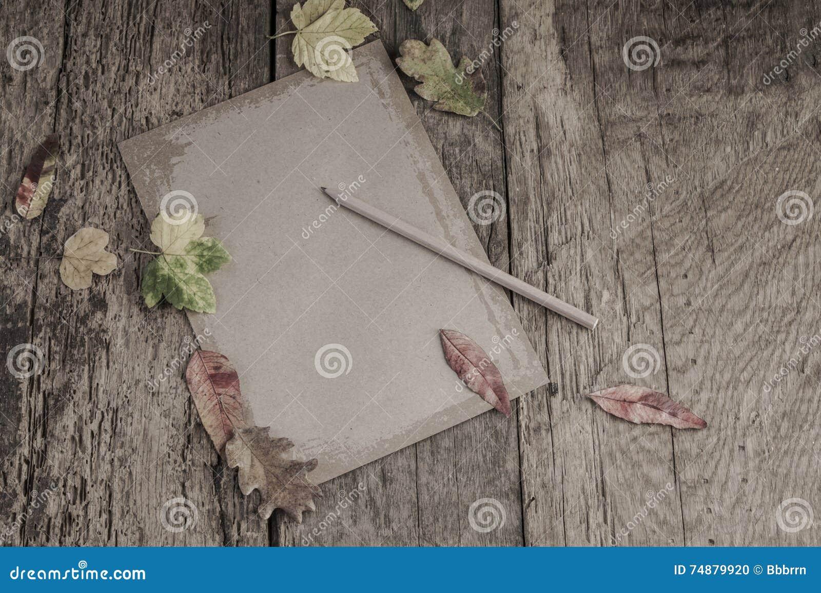 Papel na tabela de madeira decorada com folhas secadas