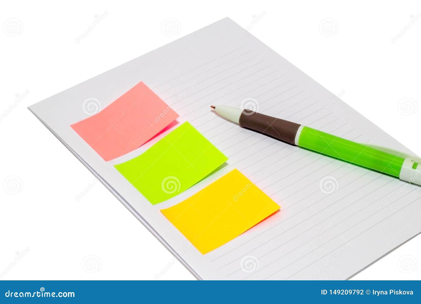 Papel pegajoso com ?rea vazia para o texto ou a mensagem, caderno aberto, e pena ao lado Isolado