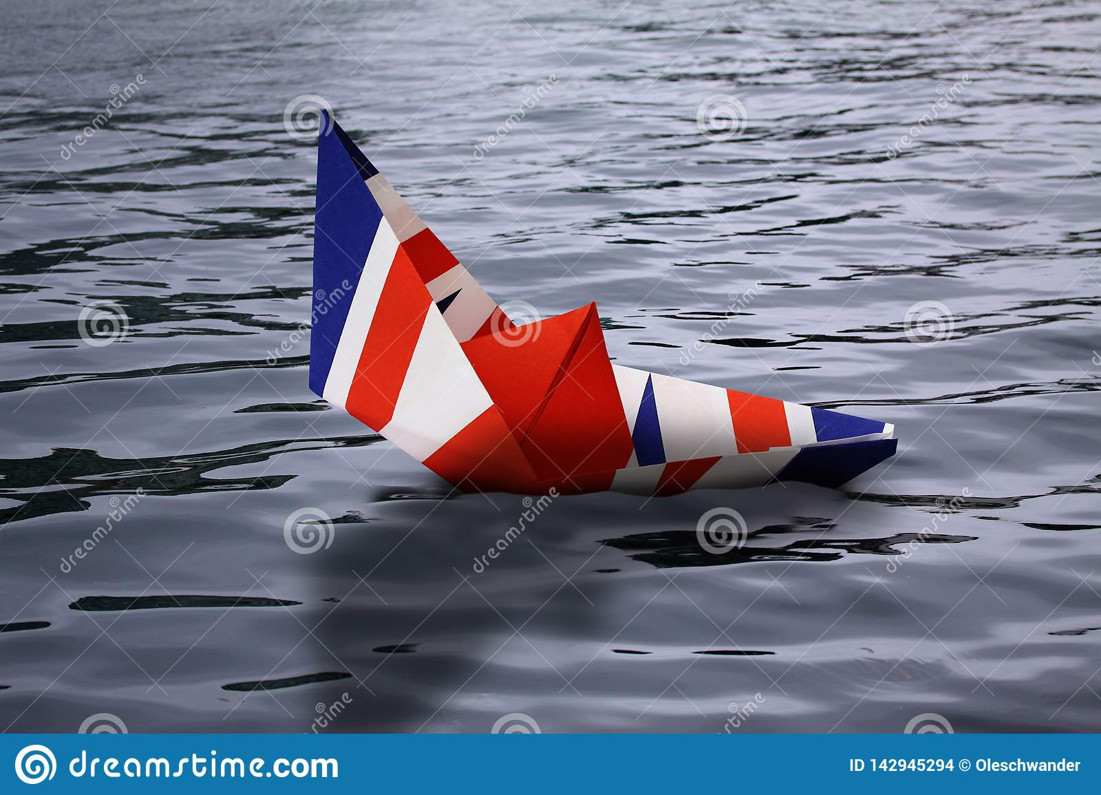 Paper boat made as the british flag sinking In water - concept showing England leaving European Union and the economy going down a