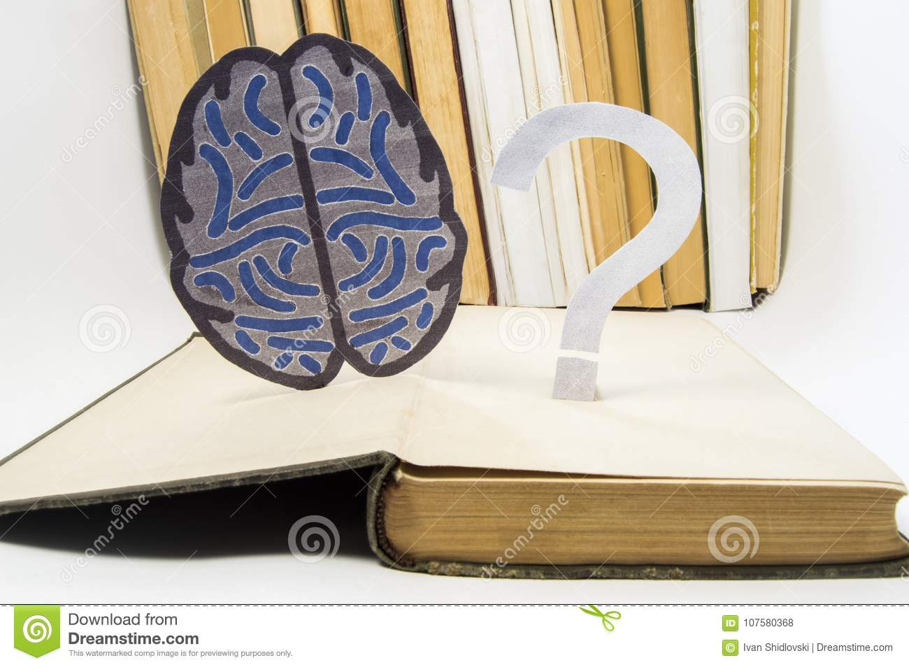 Paper brain silhouette and question mark is over old open medical book. Photo to refer issues and questions in study of brain, as