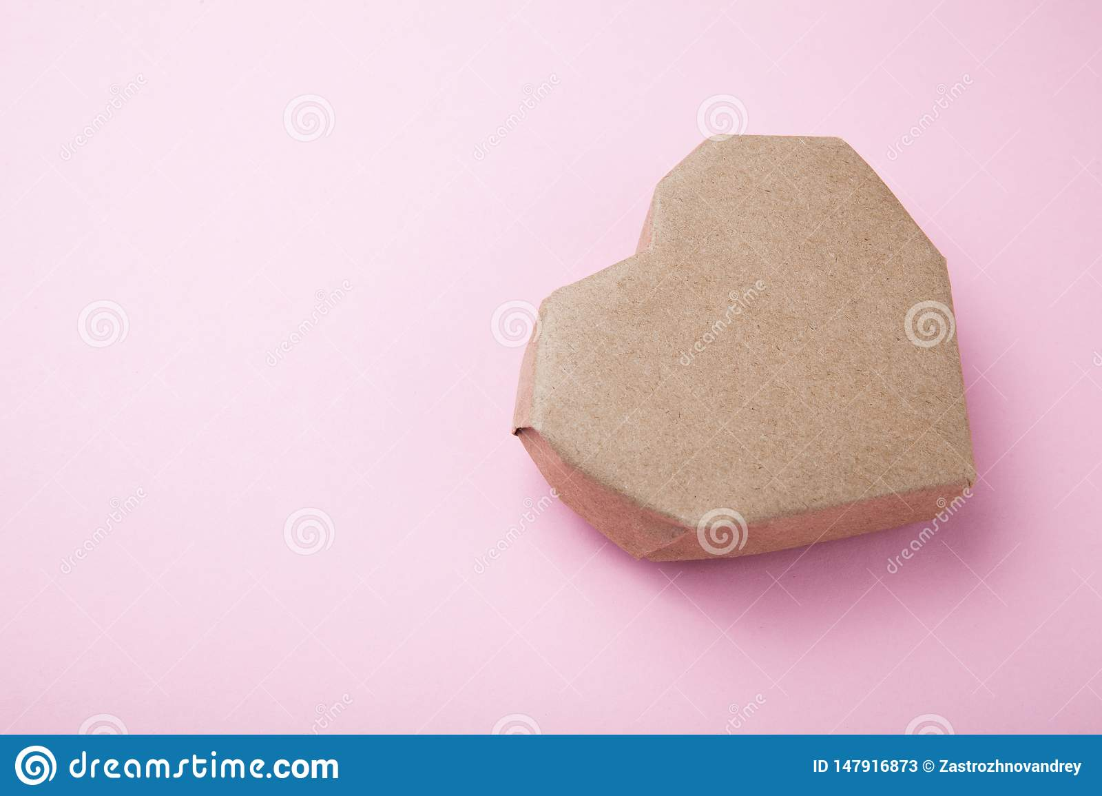 Paper brown heart on a pink background. Copy space for text