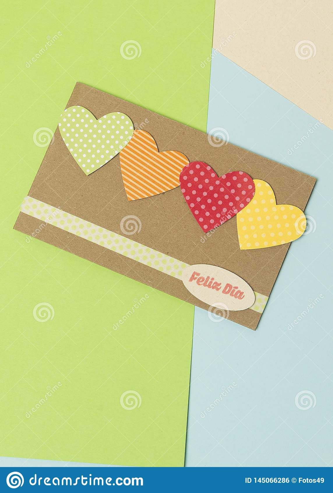 Paper card with hearts with happy day spanish phrase and blue and yellow green colors