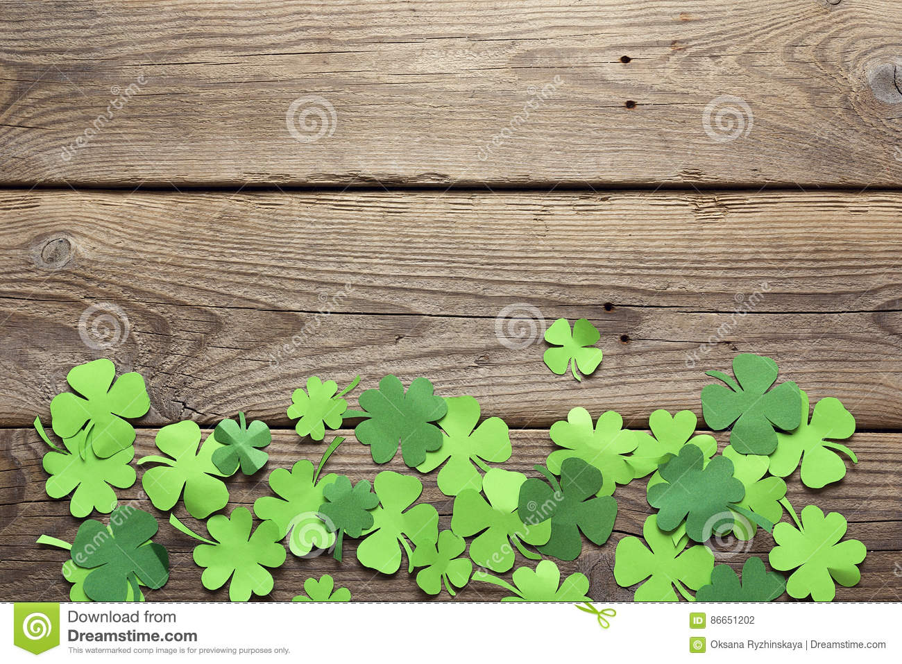 Paper clover leaves on the old wooden background. Lucky shamrock