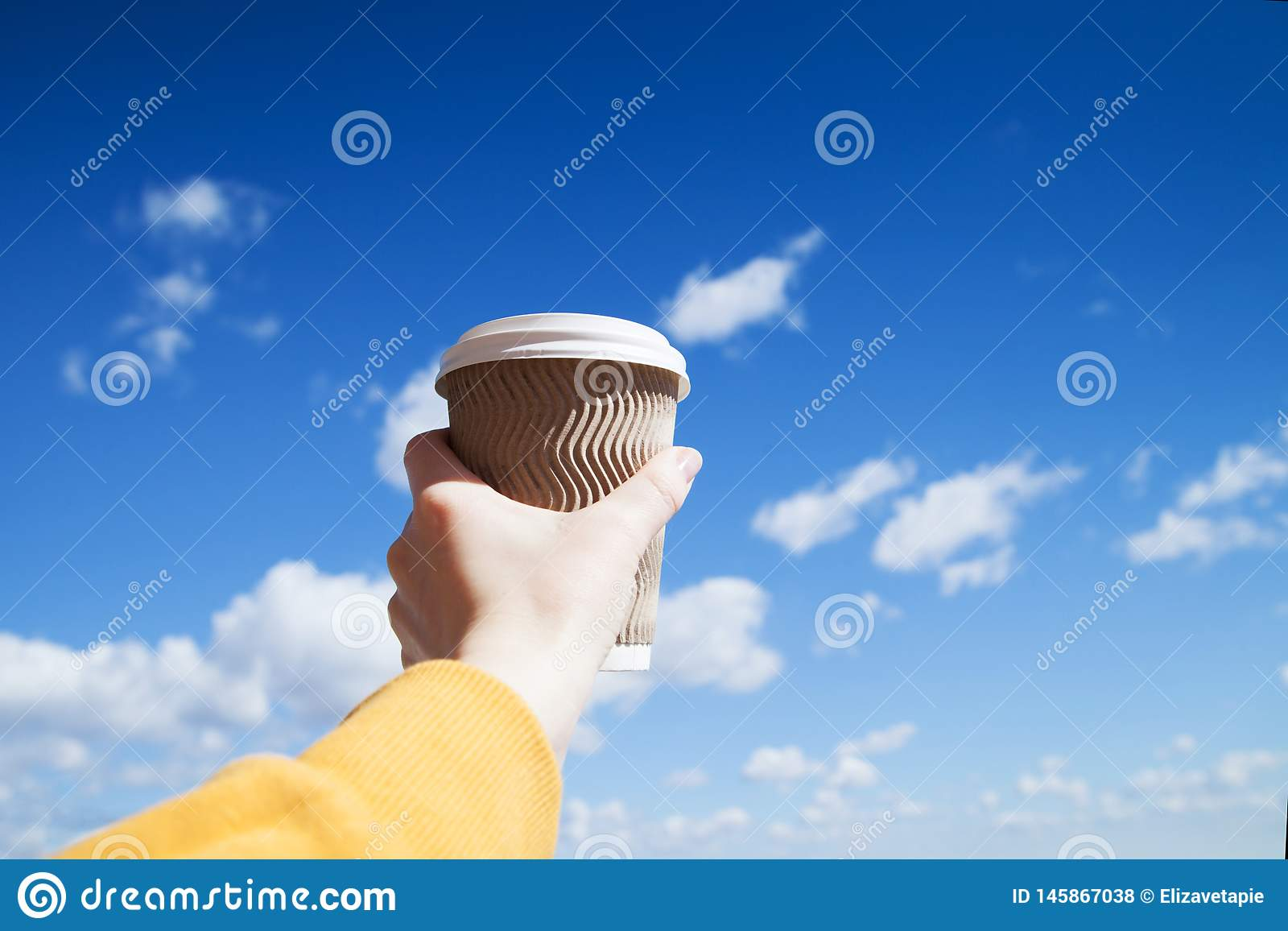 Paper cup of coffee in female hand