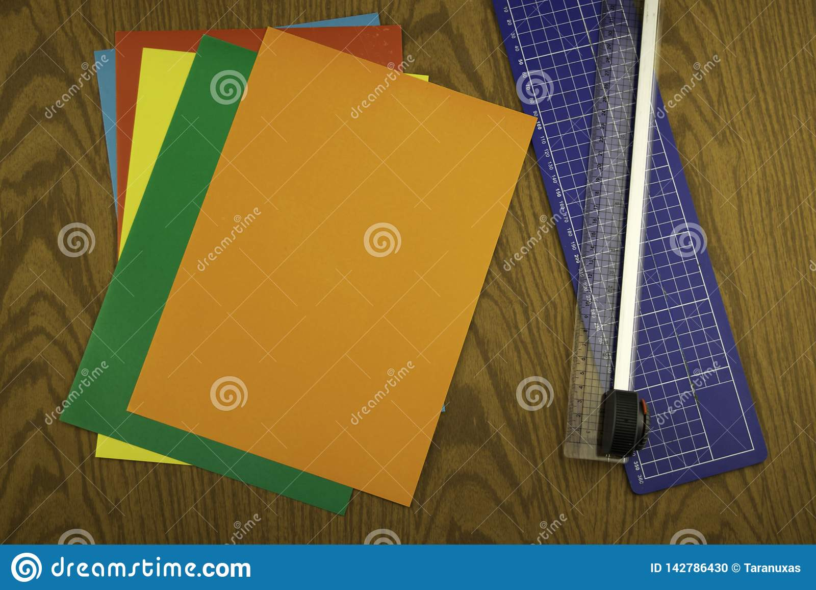 Paper cutter and color origami paper on a wooden table