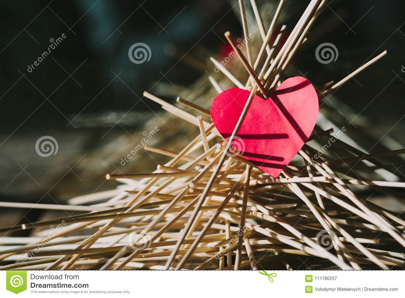 The paper heart lies on the wooden sticks. conceptual