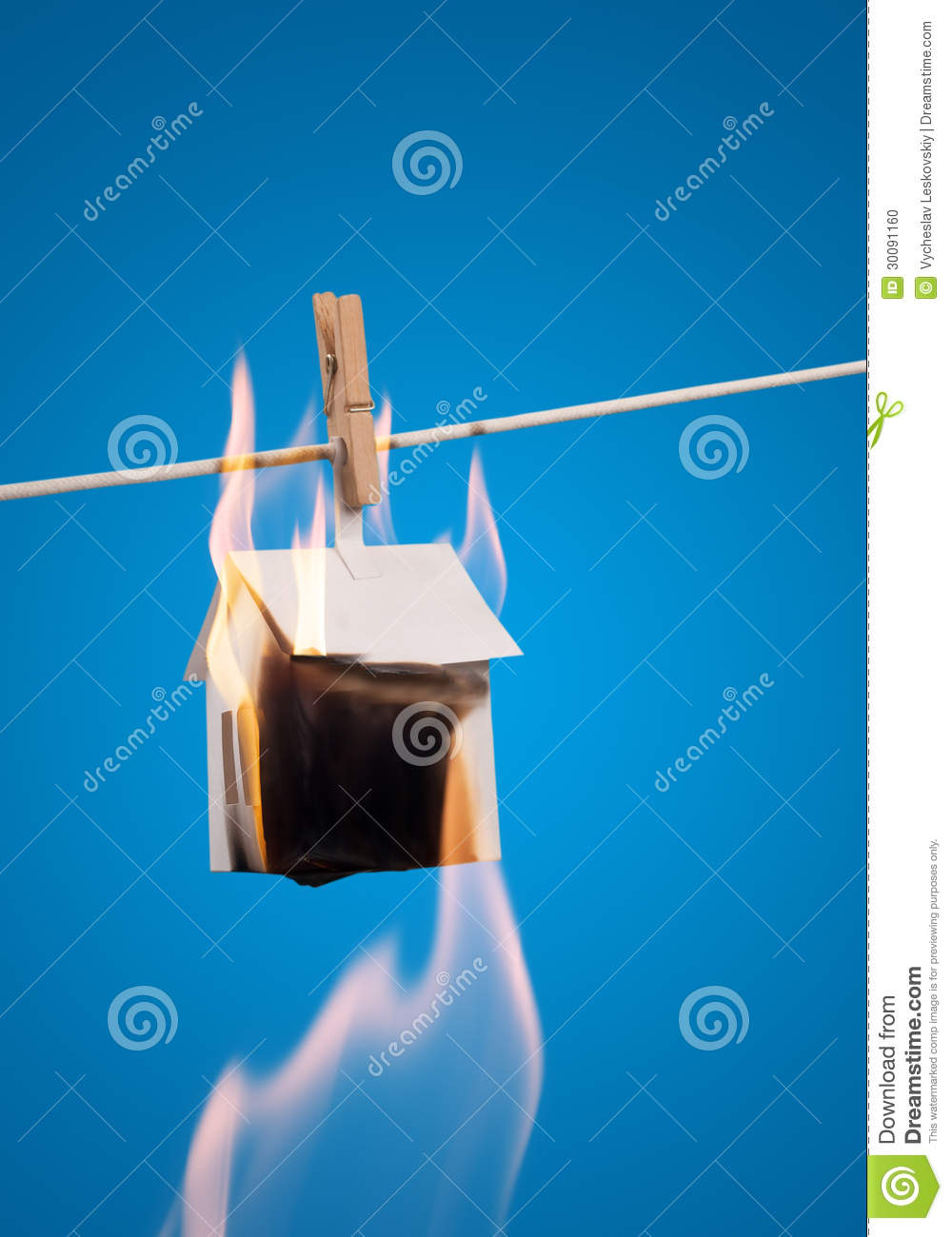 Paper house in a fire over black background - stock photo