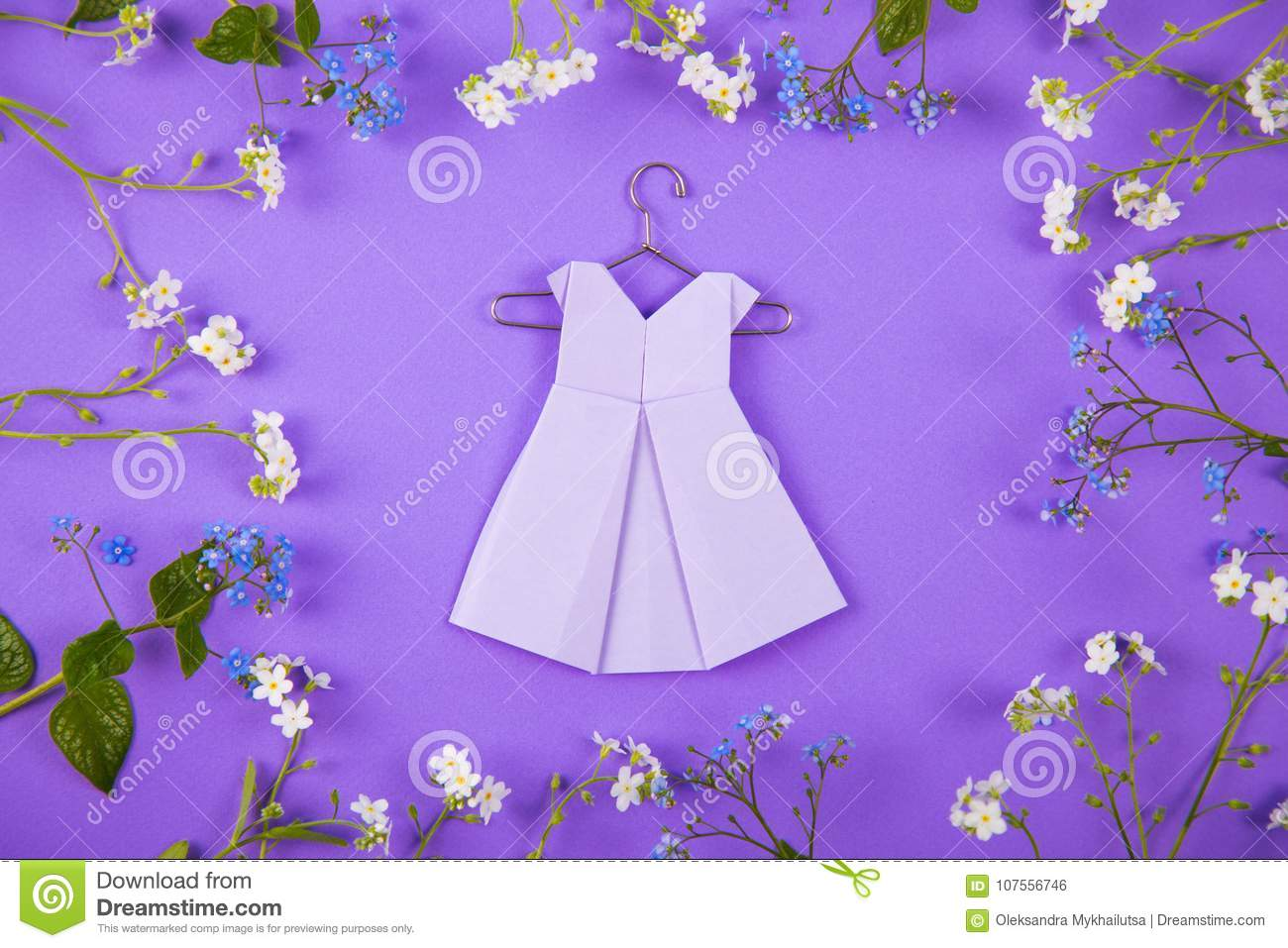 Paper Origami Dress On Hanger Surrounded With Blue And White Lit