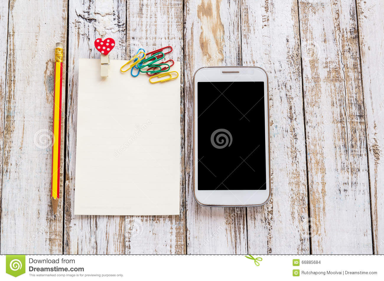 Paper and smart phone on white wooden table