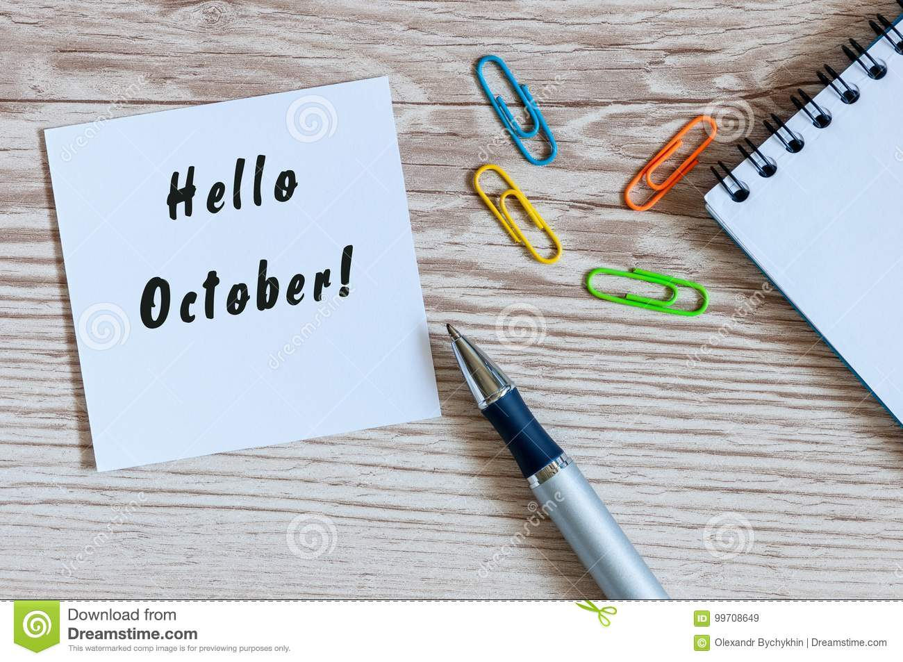 paper with words hello october and office suplies lying on wooden