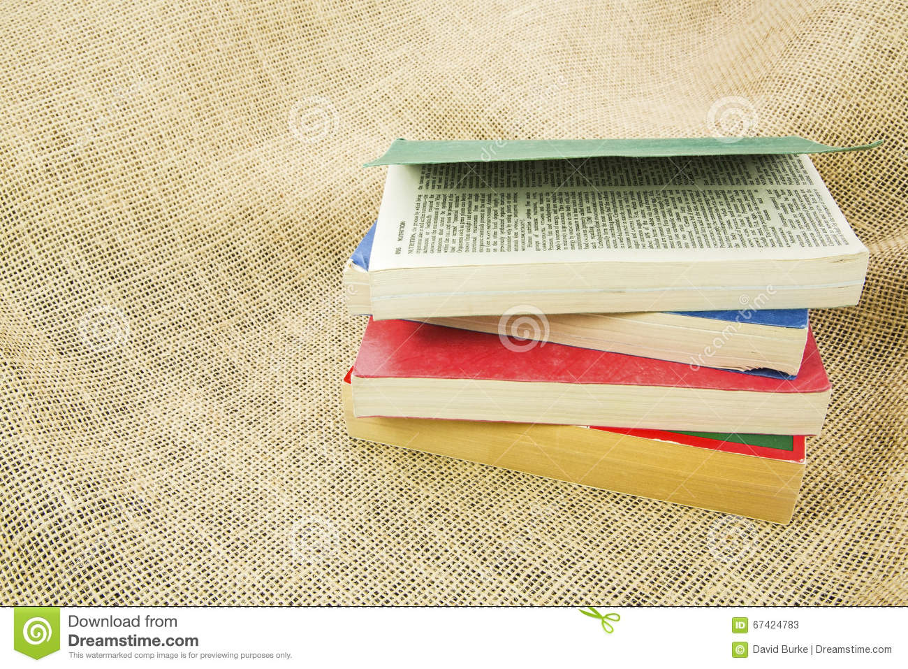 Cloth Book Covers For Sale : Paperback books piled burlap cloth background royalty free
