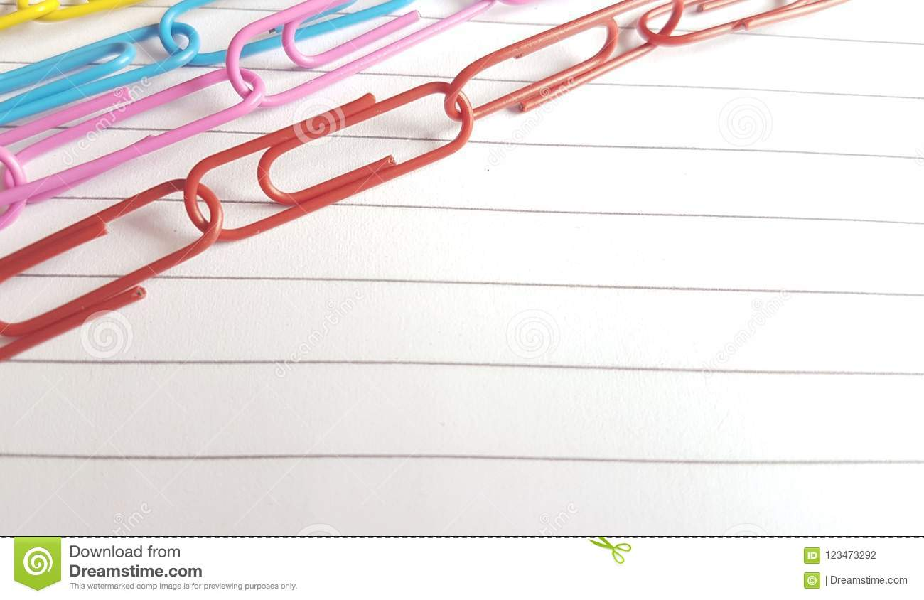 Paperclips On A Border Of White Lined Paper Background Stock