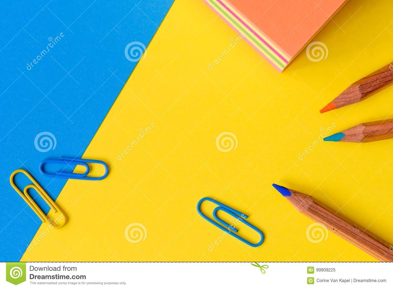 Paperclips, pencils and a memo block isolated against a blue and