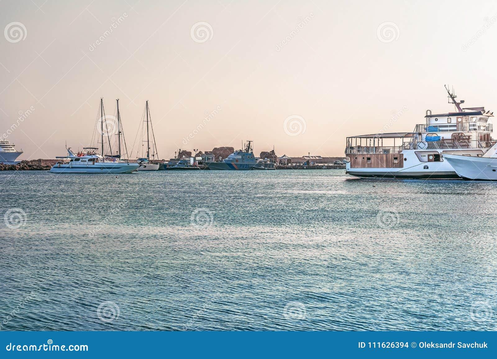 Paphos Cypern - September 20, 2016: Fragment av hamnen i Paphos i strålarna av solnedgången Fartyg och yachter tar deras ställen