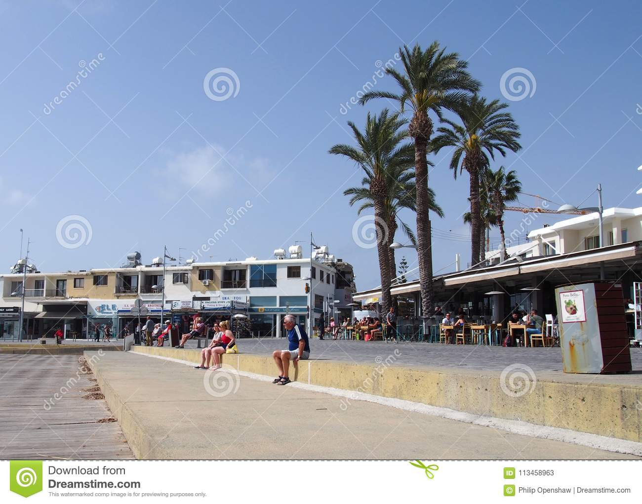 Tourists Sat On The Wall Of The Promenade In The Town Of