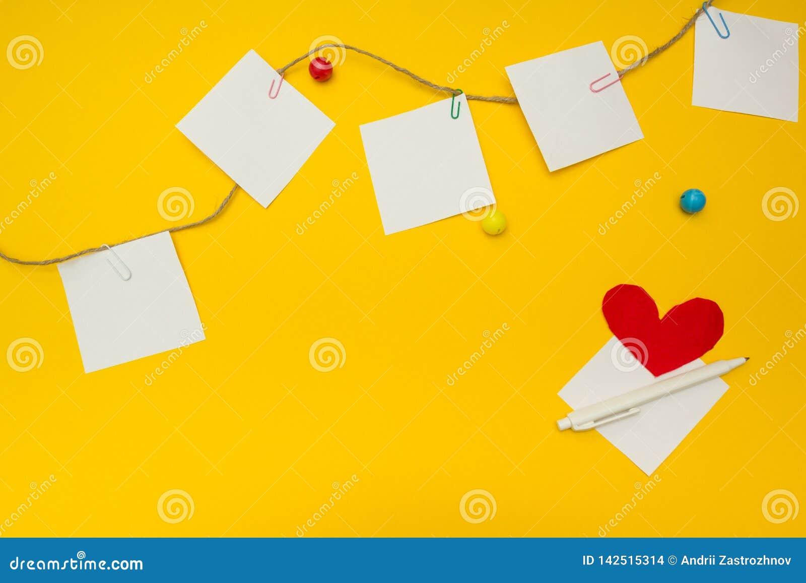 Papier, Büroklammern, Herz und Seil auf einem gelben Hintergrund, mit Raum für Text