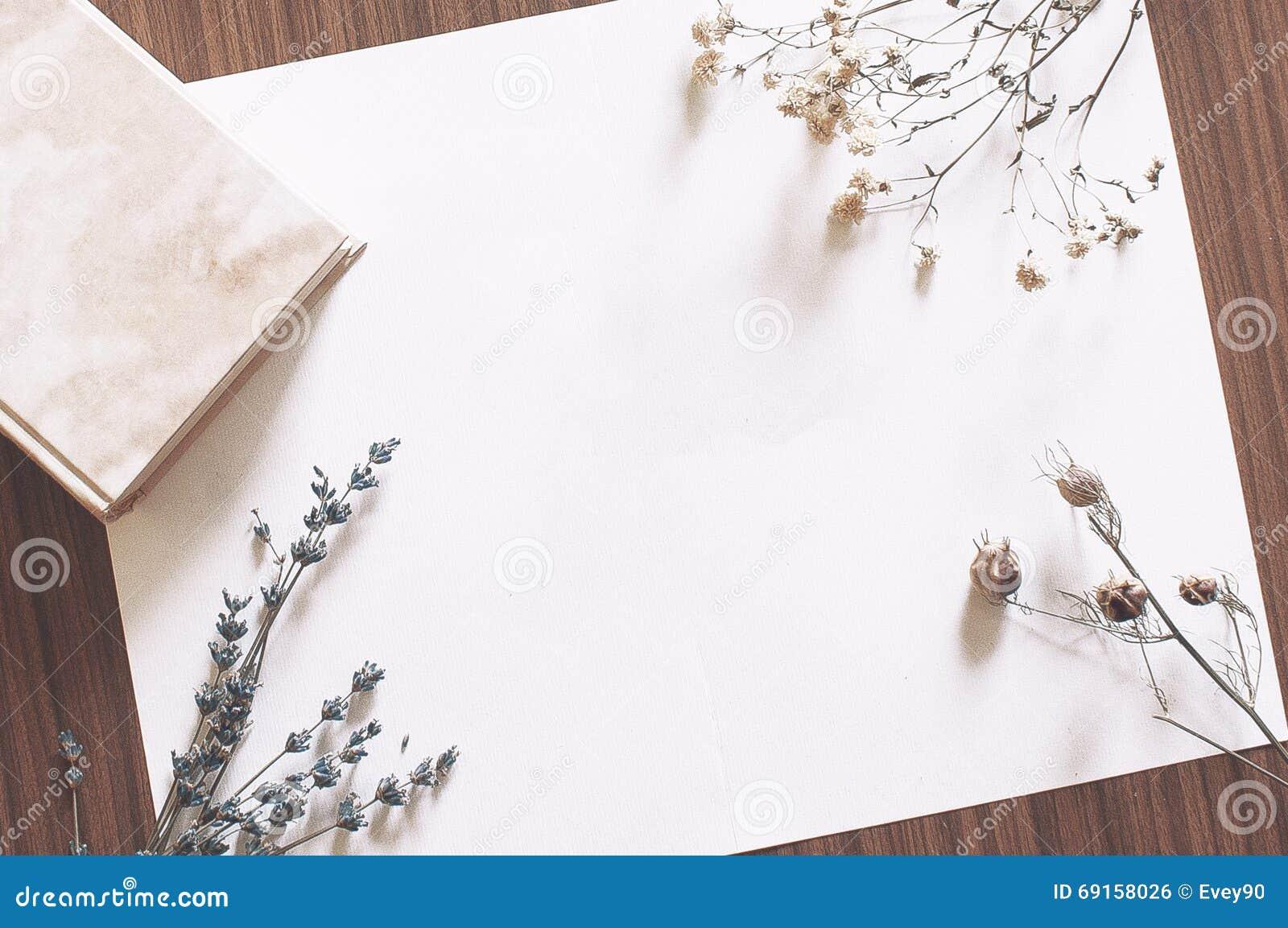 papier blanc sur le tableau avec le livre et les fleurs. Black Bedroom Furniture Sets. Home Design Ideas