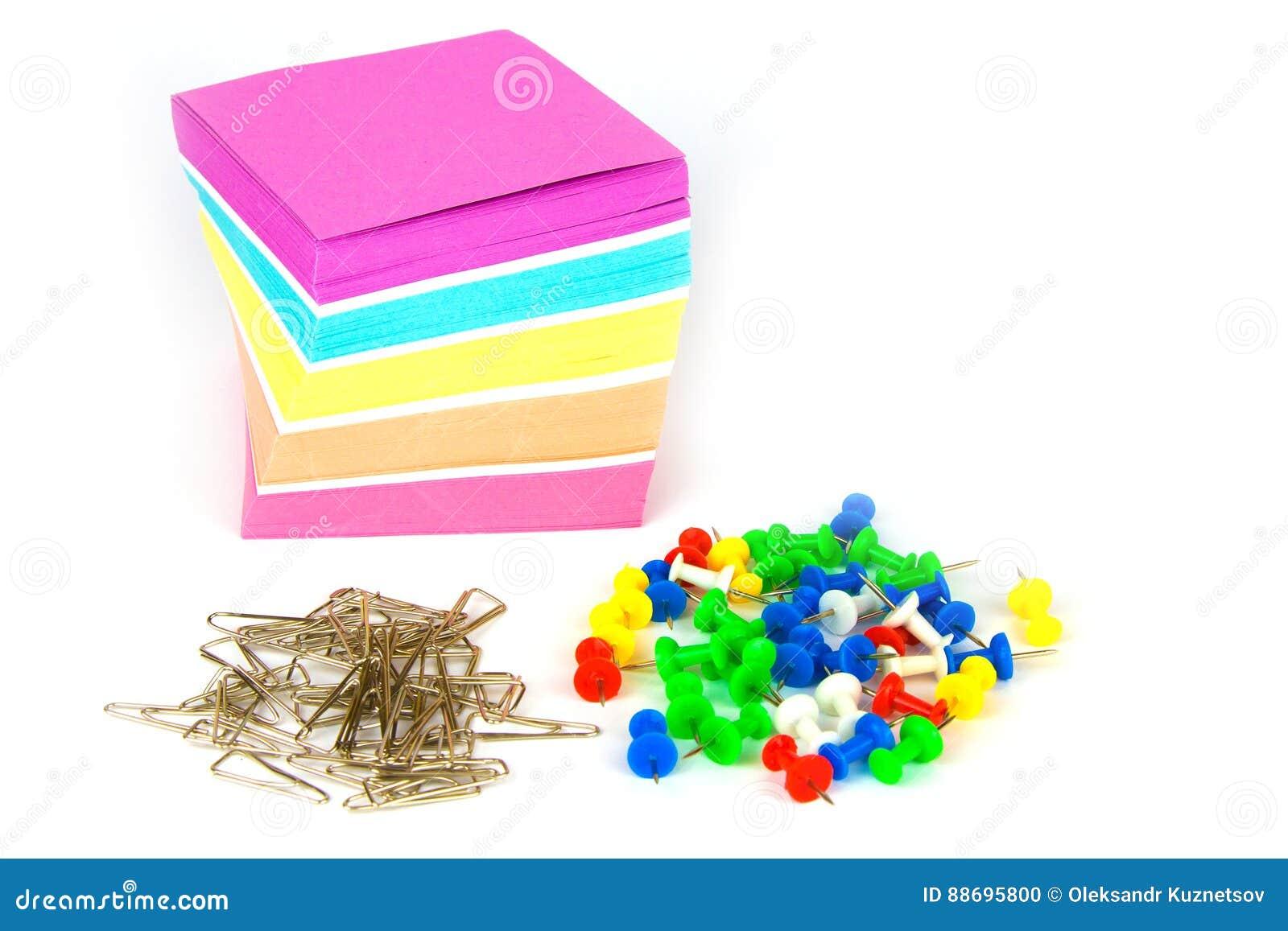 Papier, goupilles et tas colorés de note des agrafes en métal d isolement sur un fond blanc