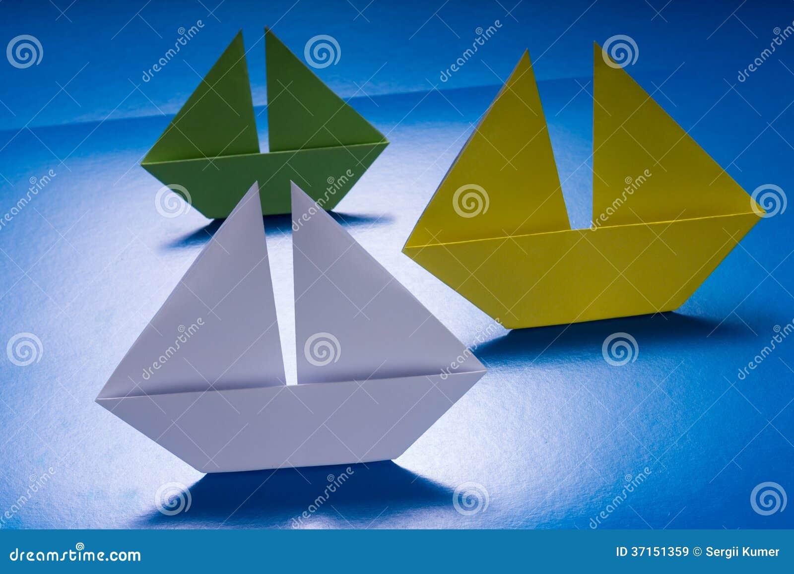 papierboote  die auf meer des blauen papiers segeln