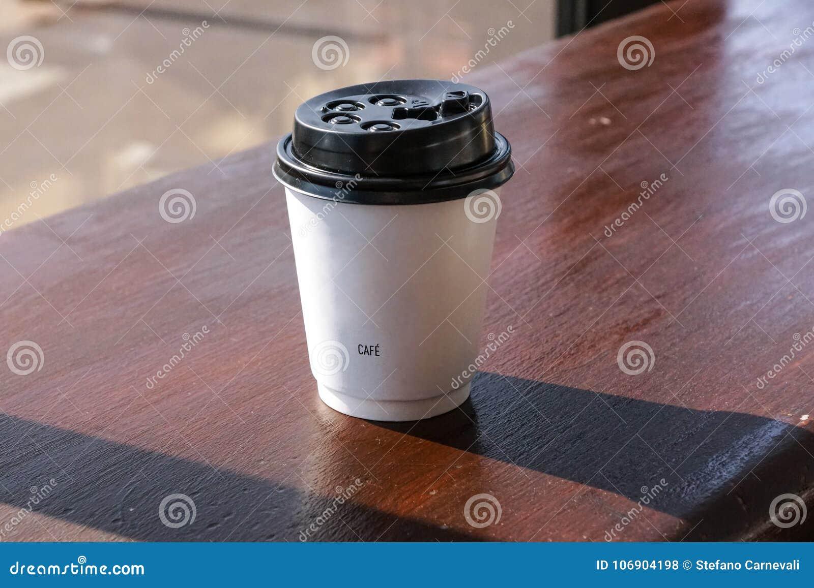 Papierowa filiżanka od sklep z kawą na drewnianym tle