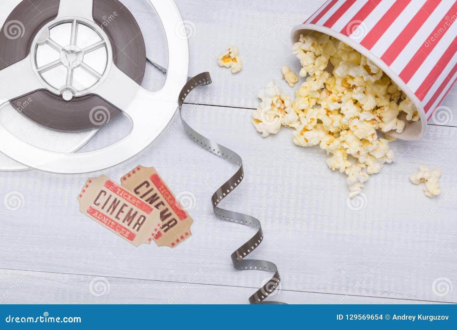 Papierowa filiżanka z popkornem, rozpraszającym obok biletów dla film sesji i filmu