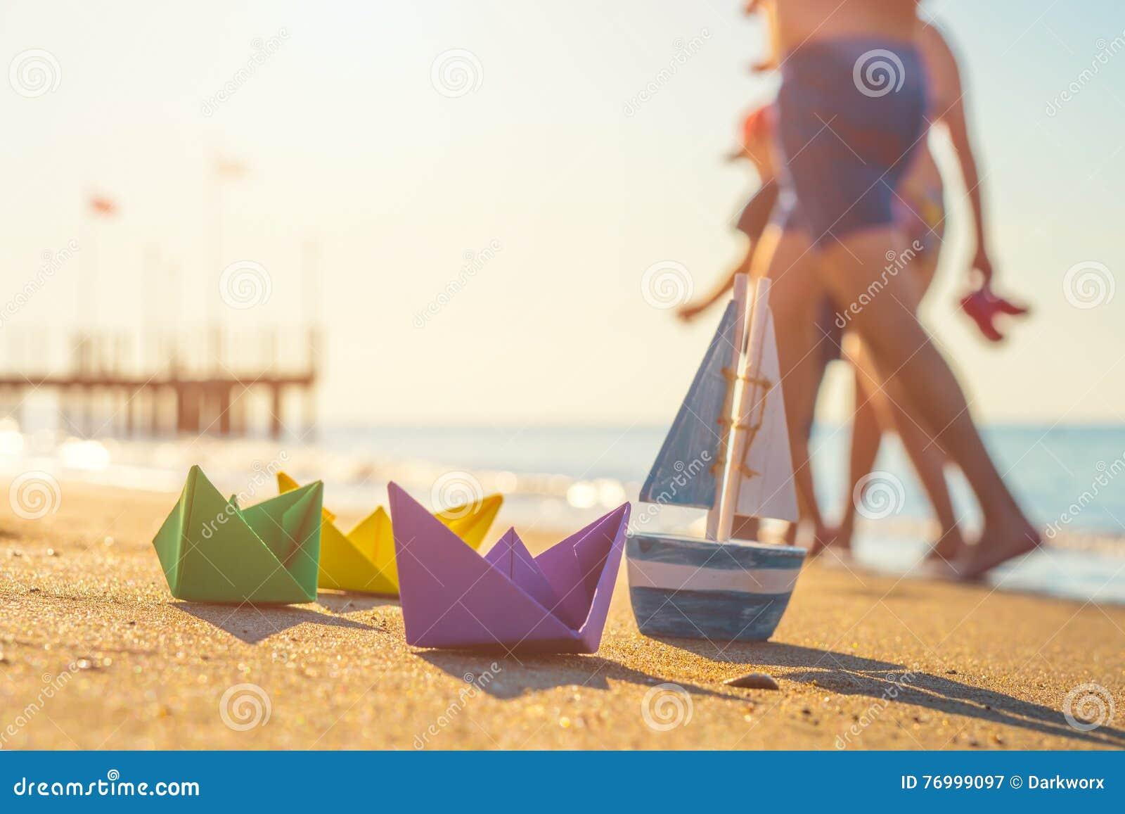Papierowe łodzie, drewniana łódź i odprowadzeń ludzie przy plażą,
