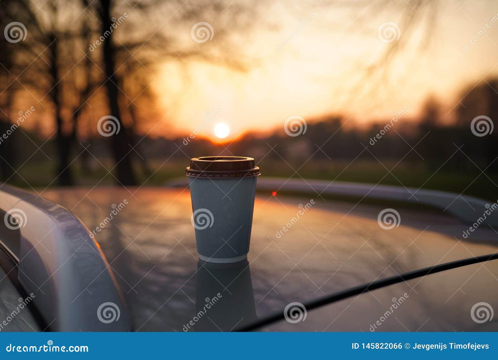 Papierowej fili?anki kawa przy zmierzch pozycj? na samochodowym dachu z pi?knym z ostro?ci bokeh