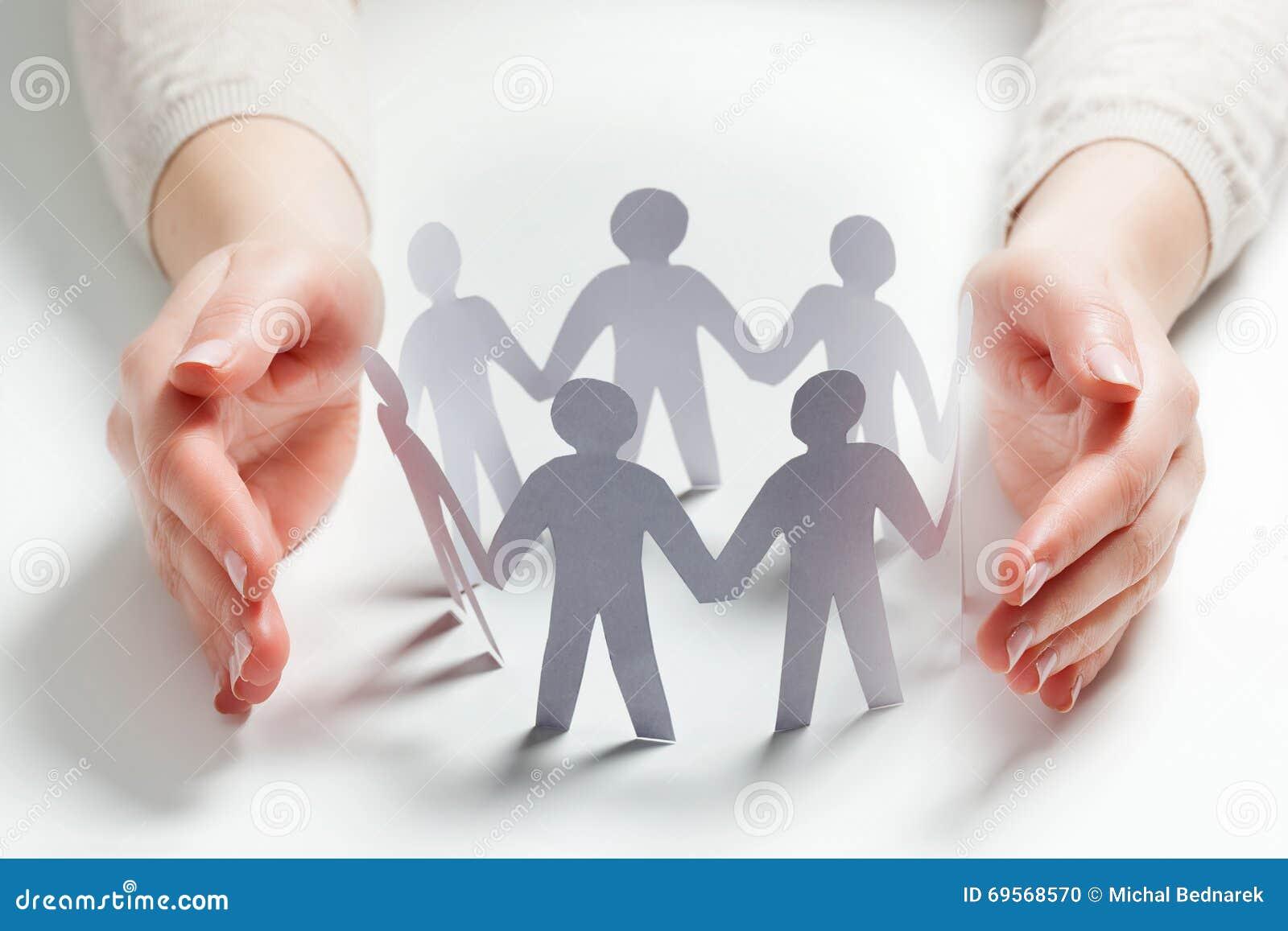 Papierowi ludzie otaczający rękami w gescie ochrona Pojęcie ubezpieczenie