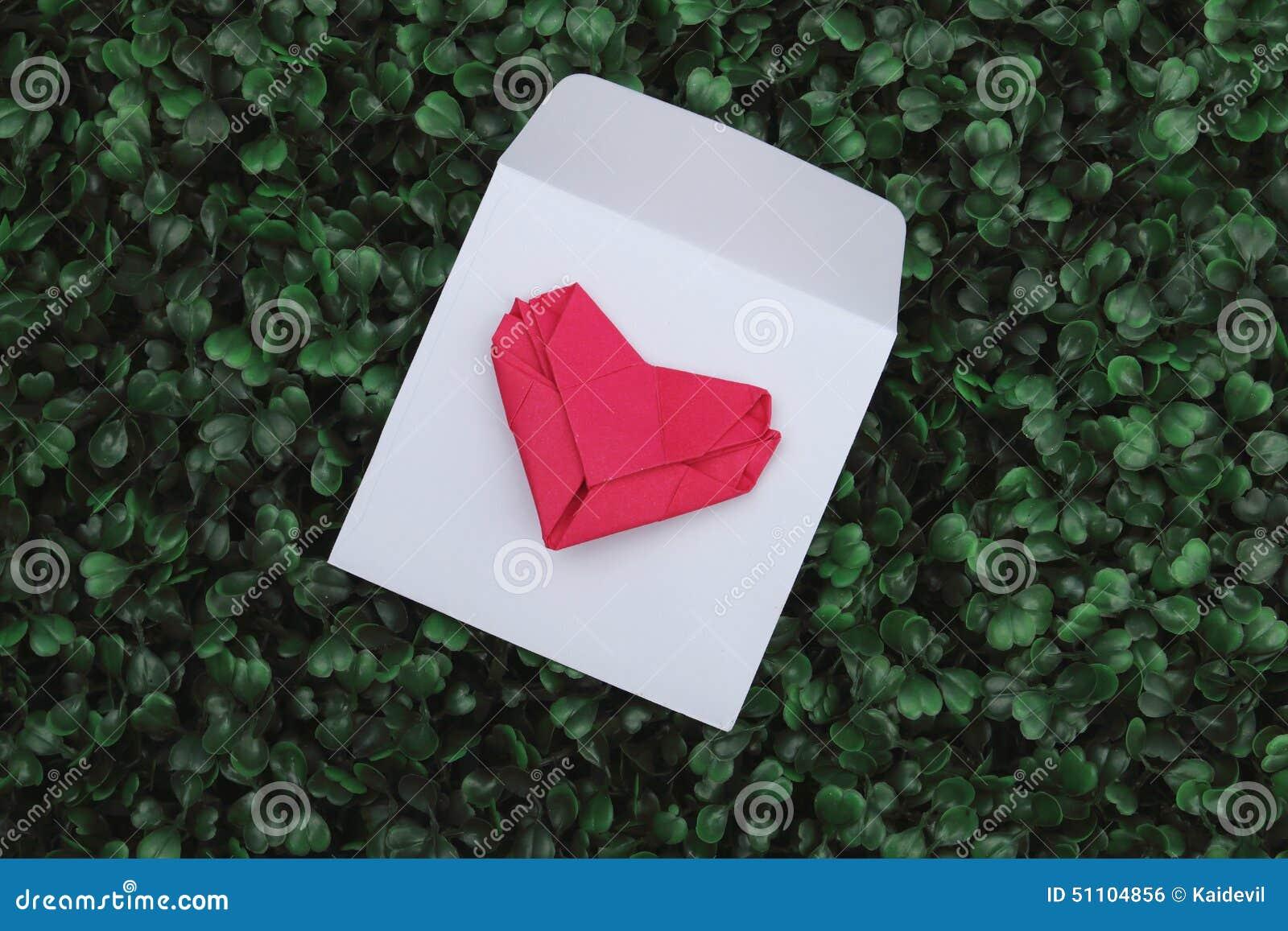 Papierowy fałdu kształta serce na białej kopercie